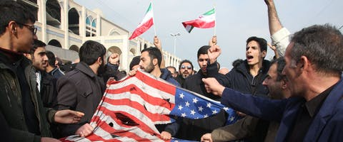 Iraniërs verscheuren een Amerikaanse vlag tijdens een demonstratie in Teheran. Zo protesteren zij tegen het doden van generaal Qasem Soleimani van de Iraanse Revolutionaire Garde op 3 januari 2020. Hij werd gedood tijdens een Amerikaanse droneaanval op het vliegveld in de Iraakse hoofdstad Bagdad. © Atta Kenare/AFP via Getty Images