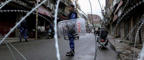 Agenten bij een wegblokkade in Jammu nadat de Indiase regering de autonomie van Jannu en Kashmir heeft ingetrokken.