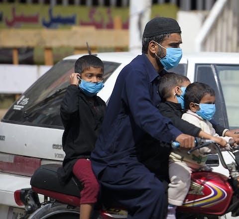 Een man en zijn kinderen rijden met mondmaskers als bescherming tegen corona door Rawalpindi in Pakistan, 25 maart 2020.