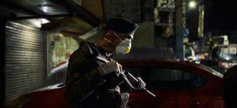 Een Filipijnse militair controleert mensen op straat tijdens een lockdown vanwege het coronavirus.