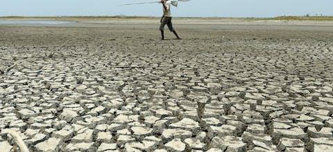 Een man loopt in India over een stuk uitgedroogd land