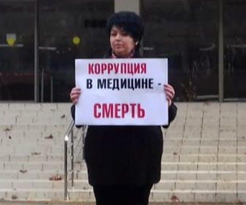 De Russische arts Yulia Volkova kan een fikse boete krijgen omdat ze kritiek uitte op de corona-aanpak in haar land. Op het bord staat: corruptie in geneeskunde = de dood.