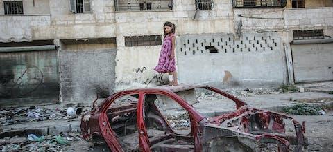 Een meisje op een autowrak in de wijk Al-Mashhad in Aleppo, september 2015