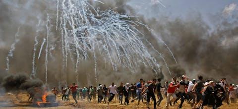 Palestijnen vluchten voor traangasgranaten tijdens botsingen met Israëlische veiligheidstroepen aan de grens met Israël en de Gazastrook, mei 2018.