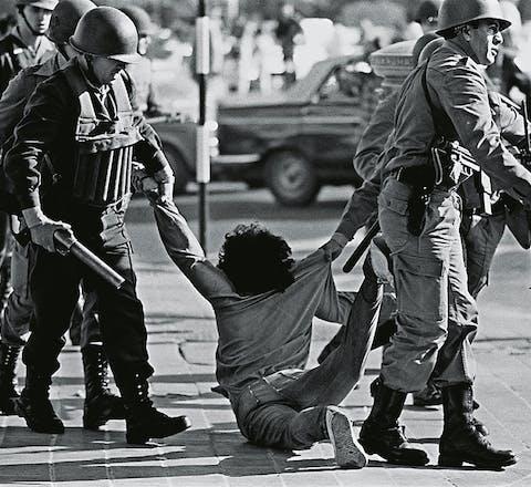 Een demonstrant wordt in 1982 opgepakt tijdens een protest tegen het regime.