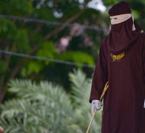 Een lid van sharia-politie staat klaar voor het geven van openbare stokslagen in Atjeh