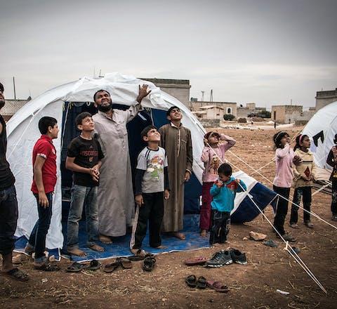 Syriërs kijken eind oktober naar een Russisch gevechtsvliegtuig boven een vluchtelingenkamp ten zuiden van Aleppo.
