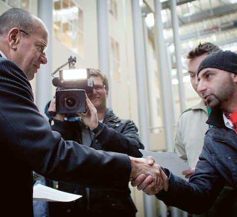 November 2012: een van de uitgeprocedeerde asielzoekers van het tentenkamp in Den Haag biedt staatssecretaris Teeven een petitie aan.